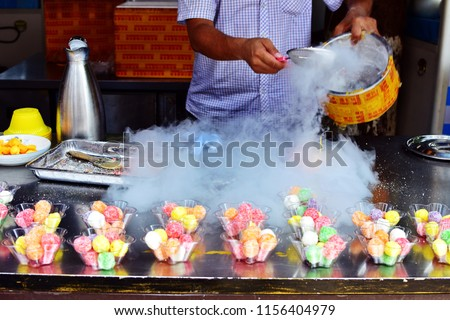 Man preparation dried ice for decoration shop and row colorful dessert in clear plastic bowl in front of stalls of store, selective focus, showcase pastry shop in China, attractive Asian dessert theme