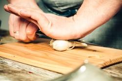 man prepares food crushes garlic