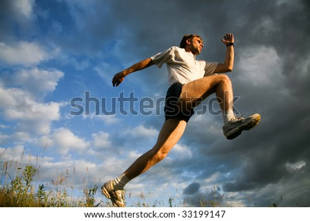 Man prepares for jump on a sky background