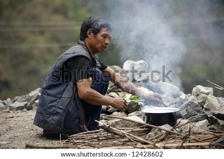 man preparing food in a pot with fire wood, annapurna, nepal