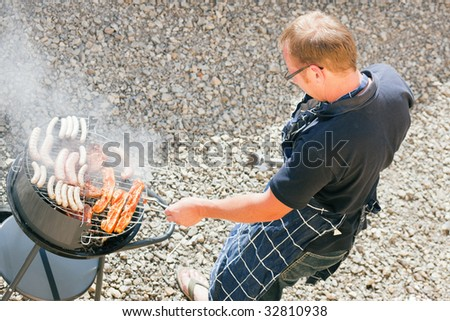 man preparing meat and sausages using a barbecue grill