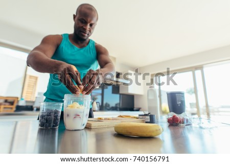 Man preparing milk shake in kitchen. Athletic man adding fruits to jar of milk.