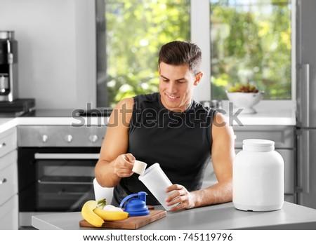 Man preparing protein shake in kitchen