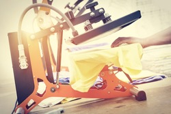 Man preparing t-shirt for printing in the silk screen printing machine