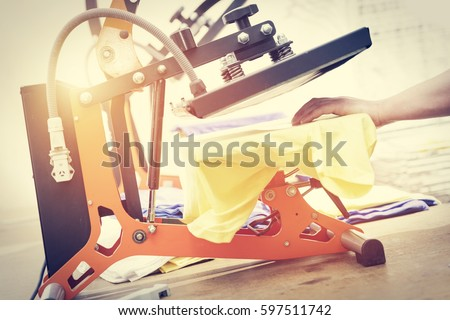Man preparing t-shirt for printing in the silk screen printing machine