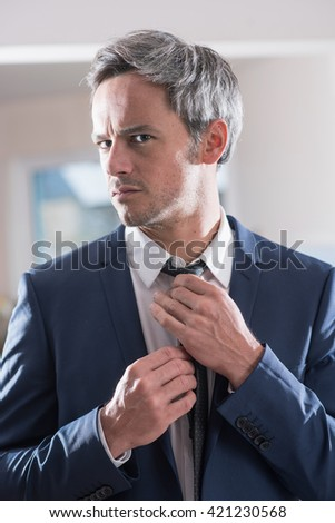 Shutterstock Man preparing to go to an important appointment, he is looking at the mirror adjusting his tie