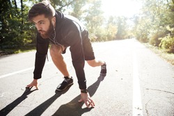 Man preparing to run in park. front view