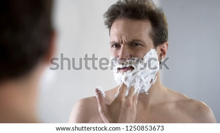 Man preparing to shave, feeling discomfort and tingle on face from shaving foam #1250853673