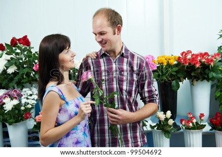 Man presenting flower to girl at shop on a date