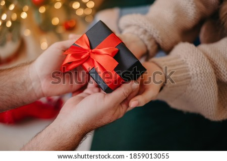 Photo of  Man presenting gift box with jewelry to beloved, hands close-up, New Year celebration