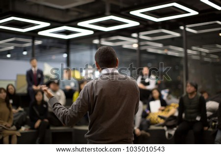 Man Presenting to Group of People #1035010543
