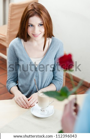 Man presents a red rose to his girlfriend at the cafe