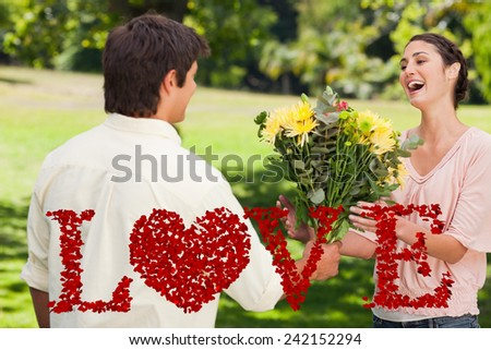 Man presents his friend with flowers against love spelled out in petals