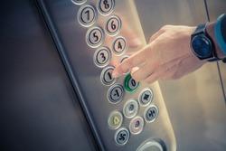 Man pressing the button in the elevator interior