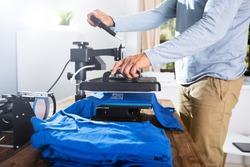 Man Printing Image On T-Shirt In Workshop