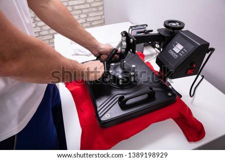 Man printing on t shirt in workshop #1389198929
