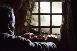 Man prisoner watching out from underground window, hands on the wall