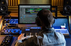 Man produce electronic music in project home studio.