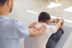 Man professional doctor osteopath fixing and stretching mans back with hands during exersicing on fitness mat at rehabilitation theapy in manual therapy clinic, top view. Chiropractor during work