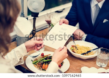 Man proposing girlfriend with card