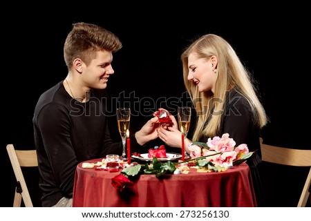 Man proposing marriage to a surprised woman on black background