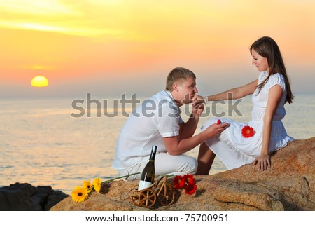 Man proposing to girlfriend and offering engagement ring