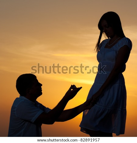 Man proposing to girlfriend and offering engagement ring. Silhouette