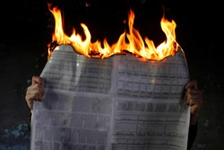 Man protesting fake media news, burning newspaper, dark mode.Burning newspapers in the hand of a man.Against the dark background