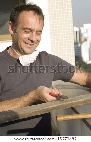 Man pulling nail with pliers. He is smiling and looking at the nail. He has a mask around his neck. Vertically framed shot.