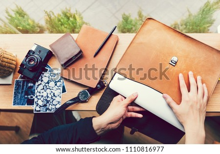 Man pulling out a laptop out of a leather case