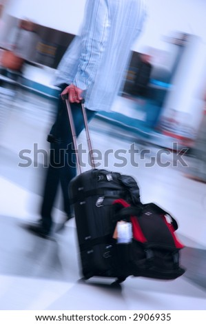 Man pulling suitcase through a busy airport