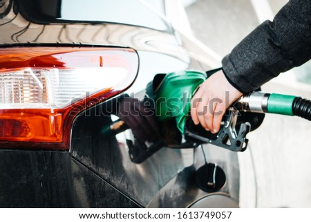 Man pumping petrol at gas station into vehicle. Hand holding a pistol  pump.