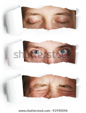 Man pursing eyes through paper hole