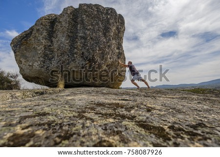 Man pushing a boulder on a rock #758087926