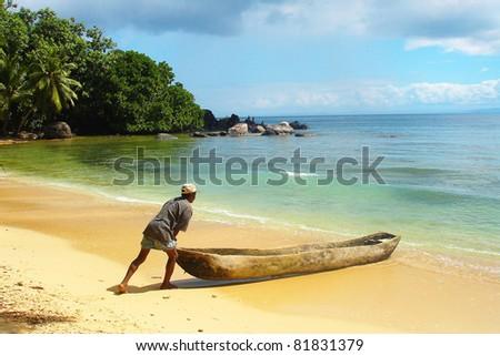 Man pushing a traditional canoe in Madagascar