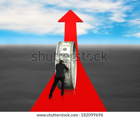 Man pushing money circle on red arrow blue sky background