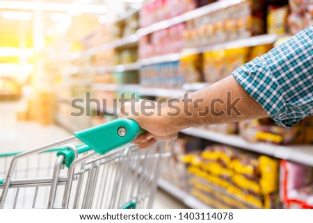 Man pushing shopping trolly in the supermarket aisles, shopping concept