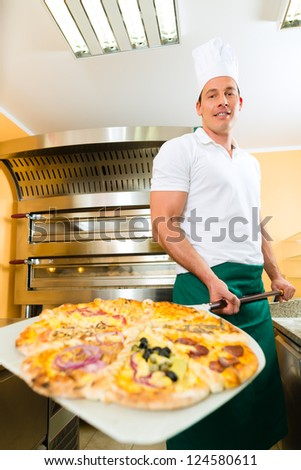 Man pushing the finished pizza from the oven with the pizza shovel