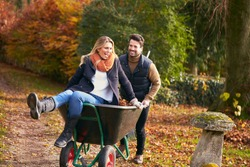Man Pushing Woman In Wheelbarrow As Couple Rake Autumn Leaves From Garden Together