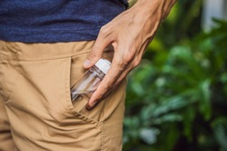 man put a hand sanitizer gel into his trouser pocket when he is going to go outside during corovid -19 outbreak crisis, take care of personal health