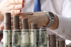 Man put coin on back his hand, counting money. Effective and useful ways to save money. Money works and brings income. Man has free capital. Invest money in order to have constant monthly profit