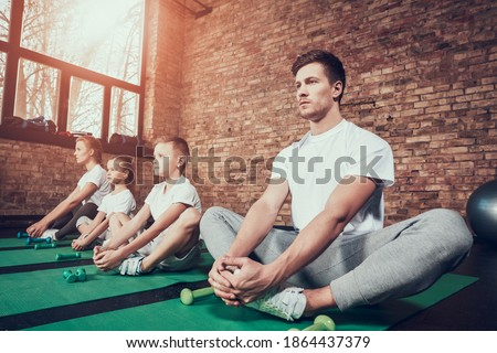 Man put his legs together and holds them with his hands. Young family sitting on a mat in the gym perform muscle building exercise.  Stock photo ©