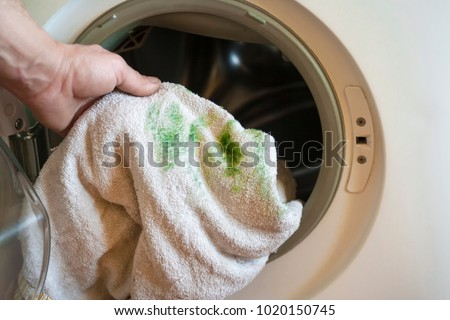Man puts a dirty towel, stained with grass, in a washing machine