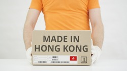Man puts cardboard box with MADE IN HONG KONG text on the table