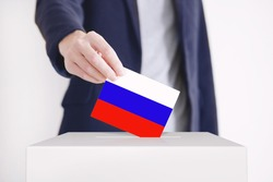 Man putting a ballot with Russian Fag into a voting box.