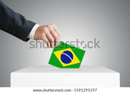 Man putting a voting ballot into a box with Brazilian flag.