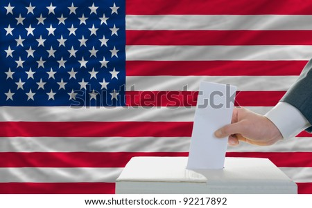 man putting ballot in a box during elections in america in front of flag