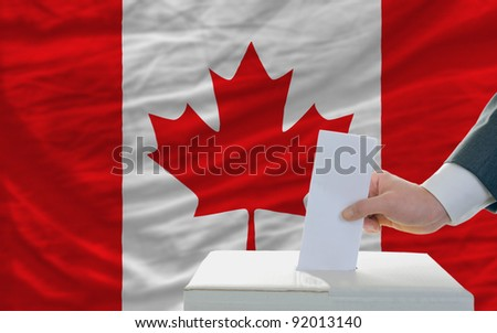 man putting ballot in a box during elections in canada