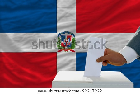 man putting ballot in a box during elections in dominican republic in front of flag