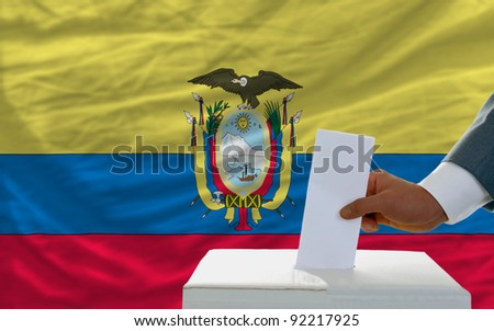 man putting ballot in a box during elections in ecuador in front of flag